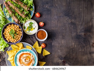Different middle eastern dishes and meze background. Hummus bowl, crispy pita chips, boiled chickpeas, meat kebab, yogurt sauce, sumac. Arab food set. Middle eastern dinner. Space for text. Top view