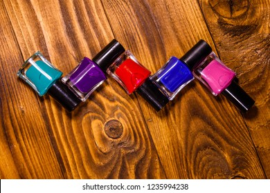 Different nail polishes on rustic wooden table. Top view