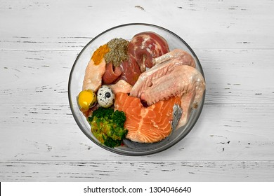 Different natural raw dog food BARF diet in bowl on white wooden background Meat fish eggs vegetables bones organic food supplement