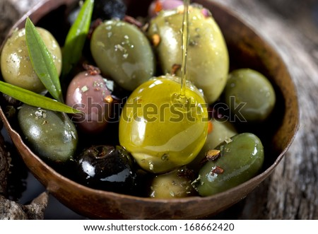 different olive fruits on wooden trunk of an olive tree