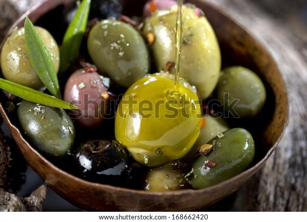 различные оливковые фрукты на деревянном стволе оливкового дерева