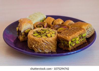 Different oriental sweets with almond on a blue plate. Close up view.
