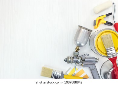 different painting tools on white background - paint brushes, can of yellow paint, spay gun, color samples