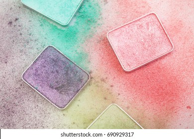 Different palettes for make-up with crumbs around on white