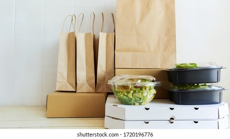 Different paper packages and containers for takeaway food on table. Takeout meal, delivery to home, food delivery, online shopping concept.