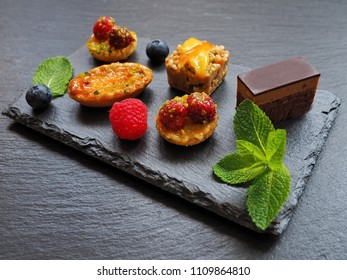 Different pastries on black stone background