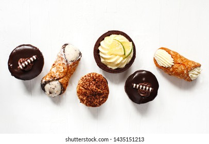 Different pastries on white background: cannoli with ricotta, tartlets filled with citrus cream, fudge cake, tiramisu cake. Top view