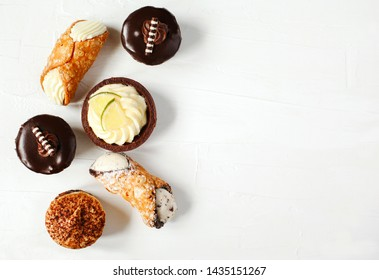 Different pastries on white background: cannoli with ricotta, tartlets filled with citrus cream, fudge cake, tiramisu cake. Top view, copy space