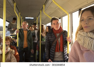 Different people can be seen standing and sitting in a bus. Some are talking, others are looking out the window.