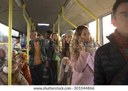 Different people can be seen traveling on the bus. Some are talking to other people, others are using technology or looking out the window.