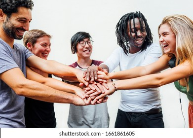 Different people putting their hands on the stack smiling