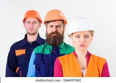 Different people in team of architects, builders, labourers, serious faces, isolated white background, defocused. Woman and men in hard hats stand close as team. Diversity in collective concept.