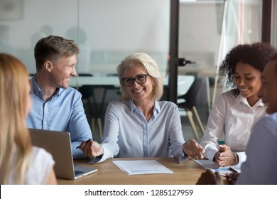 Different people young and aged multinational employees sitting around table in conference modern room discussing further cooperation or studying with middle aged instructor experienced business coach