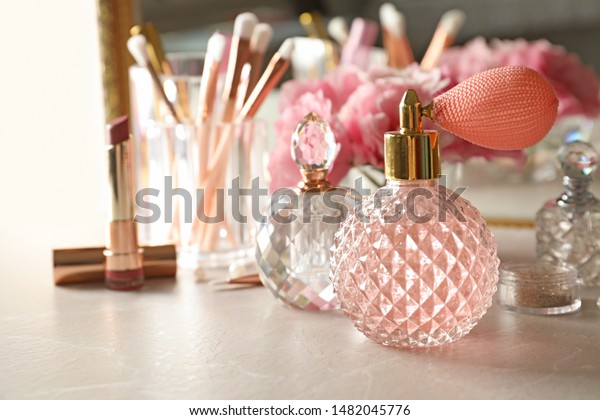 Different perfume bottles on dressing table, space for text