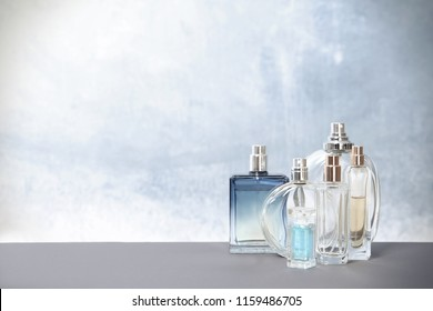 Different perfume bottles on table against color background
