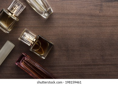 different perfume bottles on the wooden background