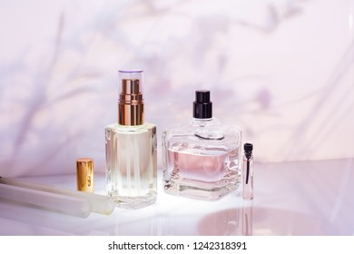 Different perfume bottles and sampler on a pink floral background. Cosmetics