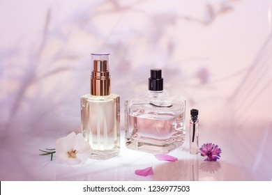 Different perfume bottles and sampler with plants on a pink floral background. Selective focus. Perfumery collection,