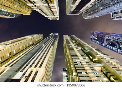 (different perspective) Stunning view from the bottom to the top of some high skyscrapers and towers illuminated during the night in Dubai Marina. Dubai, United Arab Emirates.