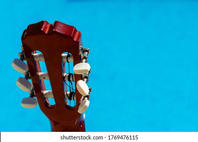 Different perspectives of the headstock of a Spanish guitar taken outdoors on a blue background