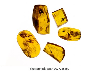 different pieces of amber on a white background. Amber of various colors and structure and shapes. Transparent and opaque pieces of amber. Natural amber