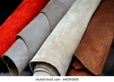 Different pieces of leather in a roll. Rawhide roll. The pieces of skin. Pieces of colored leather. The rolls of skin.