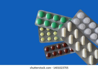 Different pills in blisters isolated on blue background. Polypharmacy