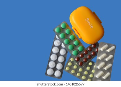 Different pills in blisters and yellow plastic medicament container isolated on blue background. Isolated. Polypharmacy