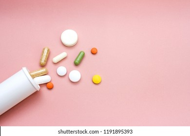 Different pills drugs or tablets spilling out of a white plastic medicine bottle aspirin or paracetamol antibiotics