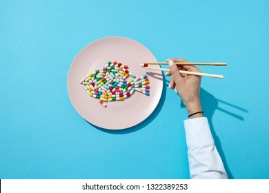 Different pills and supplements as a fish on a white plate chopsticks in woman's hands with shadows on a blue. Suppressants for dieting concept. Top view.