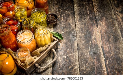 Different preserved vegetables from vegetables and mushrooms in glass jars. On a wooden background.