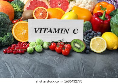 Different products and card with phrase VITAMIN C on grey table