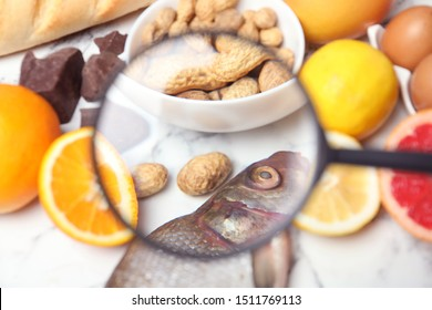 Different products with magnifier focused on fish and peanuts, closeup. Food allergy concept