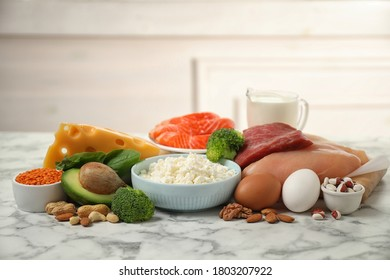 Different products rich in protein on white marble table