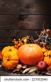 different pumpkins with nuts, berries and grain in front of wooden boards