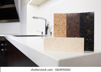 Different quartz kitchen counter top samples on white polished countertop with precise processed edges.