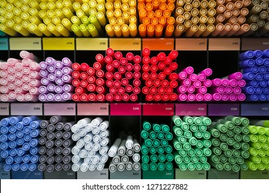 Different rainbow markers or pens on the shelfs at art store.