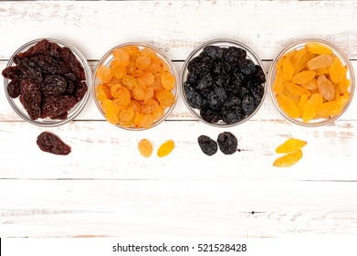 Different raisins on wooden rural white background with copy space, top view, the Vega food.