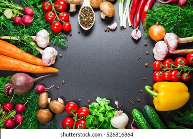 Different raw vegetables and spices on black background. Healthy eating. Autumn harvest and healthy organic food concept.