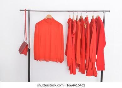 verschiedene und rote Kleidung, Mantel, Pullover, Hemd, Kleidung mit Lederhandtasche auf einem Hänger