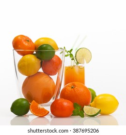 Different refreshing citrus fruits and fruit cocktail against white background; Cocktail ingredients; Vitamin suppliers; Fitness drink