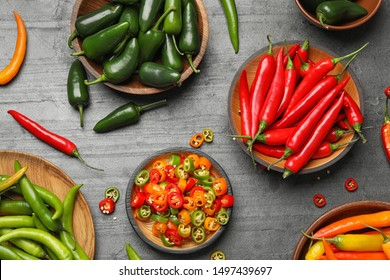 Different ripe hot chili peppers on grey table, flat lay