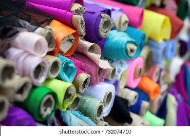 Different rolls of colorful clothing textiles in a shop. Ready to buy for manufacturing and dressmaking.