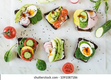 Different sandwiches with vegetables, eggs, avocado, tomato, rye bread on light marble table. View from above. Appetizer for party. Flat lay.
