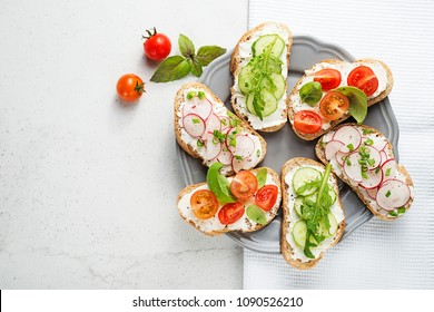 Different sandwiches with vegetables on a light gray background. top view.