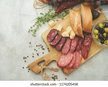 Different sausages with cheese, grapes and olive. Sliced Salami in rustic style.