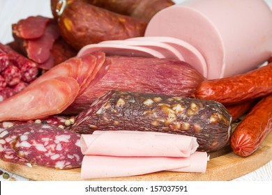 Different sausages on wooden board close up