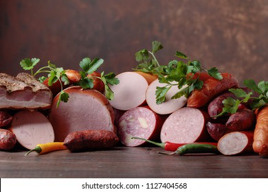 Different sausages and smoked meats on a old wooden table . Copy space .