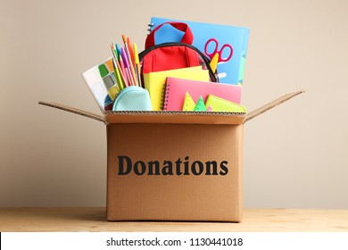 Different school supplies in a cardboard box on a neutral background. Concept donations.