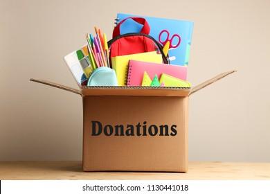 Différentes fournitures scolaires dans une boîte en carton sur fond neutre. Concept de dons.